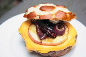 Fertiger Burger mit Laugenbrötchen, Cheddar und karamelisierten Zwiebeln