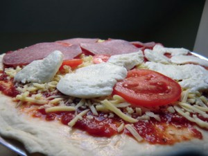 Weber Pizzastein mit frisch belegter Pizza